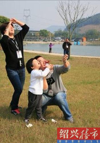一家三口享受放风筝的乐趣